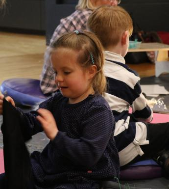 Photo of a child sitting on the floor taking part in an art workshop.