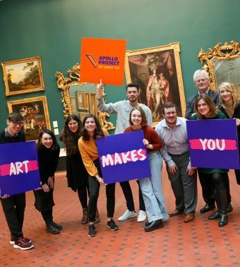 Group photo of men and women posing in an art gallery and holding colourful signs that say 'Apollo Project' and 'Art Makes You'.
