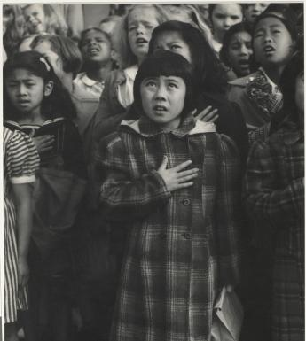 Black and white photo of children standing with one hand on their chests, pledging allegiance.