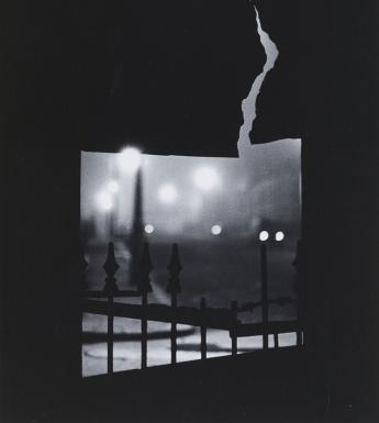 Black and white fine-art photograph of a gloomy city night scene viewed through a crack in a fence.