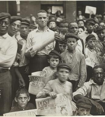 Black and white photo from 1908 showing a group of newsboys and men crowded together on the street