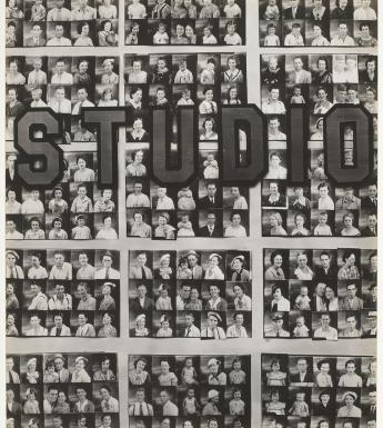 Black and white photo of a photography studio window filled with passport-size photos of people. The word studio is written on the window.