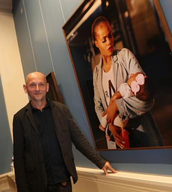 Photo of a man posing in a gallery beside a large fine-art photograph of a woman holding a child.