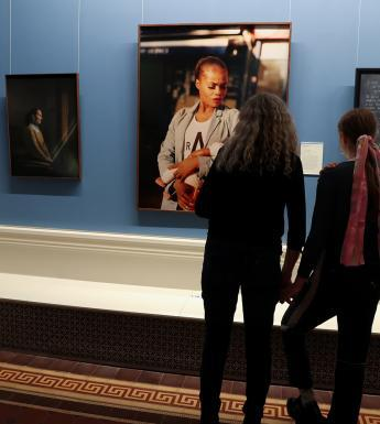 Photo of two women looking at three portraits in an exhibition
