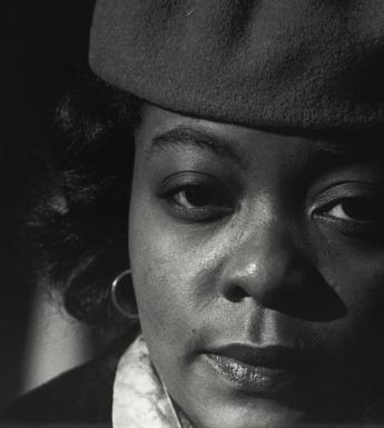 Black and white closely cropped photographic portrait of a woman wearing a hat