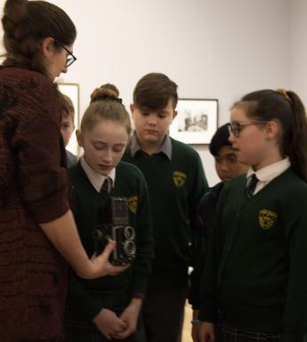 School kids looking at a vintage camera in an exhibition