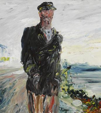 A man in a dark overcoat with his hands in his pockets, wearing a cap. In the background, the sea.