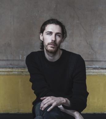 A photographic portrait. A man sits on a stool in front of a yellow and grey wall, with paint peeling. He wears a black round neck jumper, and dark jeans. His hands look as if they are in motion.