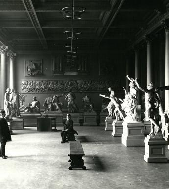 A black and white photograph of a room filled with plaster casts of sculptures. There are two me in the room - one sits on a bench in the middle of the room, the other stands on the left, facing the seated man.