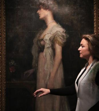 Artist Amanda Coogan standing in profile in front of a portrait of Constance Markievicz in the National Gallery of Ireland.