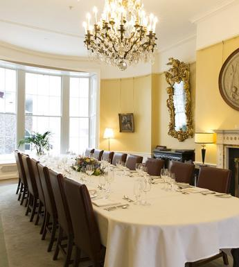 A room with dining table set up for event
