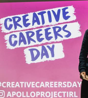 Two people stand on stage in front of a bright pink screen with the words Creative Careers Day written across it.