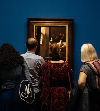 A photograph of people, with their backs to the camera, looking at three gilt-framed paintings on a blue wall.