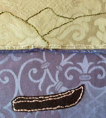 Photo of textile art showing a currach and mountains embroidered on cloth.