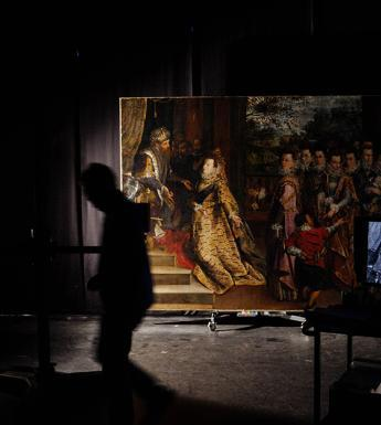 Photo of a large painting in a darkened room with silhouette of figure walking in front
