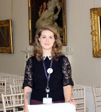 Sarah stands looking at the camera, resting her hand on a chair in front of her. Behind are chairs set out for a wedding, and hanging on the walls are three paintings in gold frames.