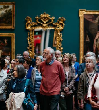 Photo of a group of people on a guided tour in a gallery, with gilt-framed pictures and mirrors on a wall behind them.