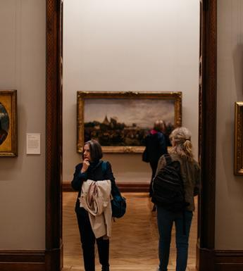 Photo of two women passing each other in a doorway in a gallery room with gilt-framed paintings on the walls.