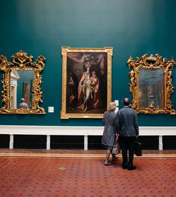 Photo of a couple standing in a gallery in front of a wall displaying gilt-framed paintings and mirrors.