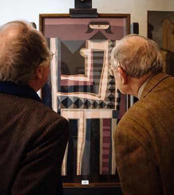 Photo of two men with their backs to the camera, looking at a painting on an easel.