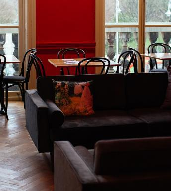 Photograph of an interior with red walls, grey couches and dining tables and chairs with large windows looking out on trees.