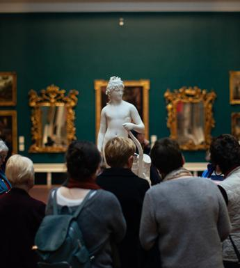 Photo of a group of people looking at a marble statue in a gallery room painted green and hung with gilt-framed paintings.