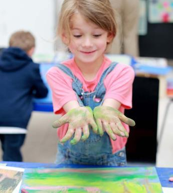 Photo of girl holding her hands, covered in green chalk, out for the camera.