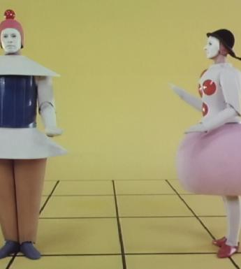 Film footage still of two figures wearing geometric costumes standing in a yellow space.