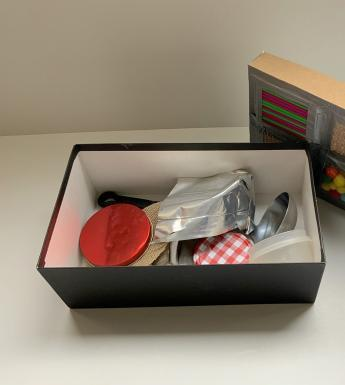 A shoe box filled with household objects, with textured materials taped to the lid