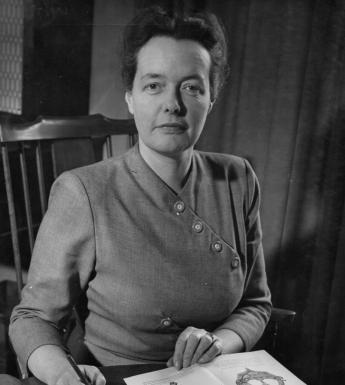 Photograph of Bea Orpen, sitting on a chair, looking at the camera with a book of her artwork open in front of her.