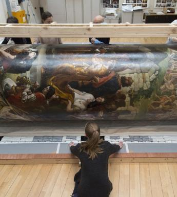 Members of the National Gallery of Ireland's conservation team rolling 'The Marriage of Strongbow and Aoife' in preparation for its move.