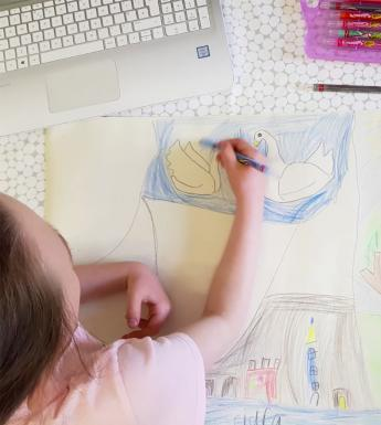 A view from above of a child drawing a picture