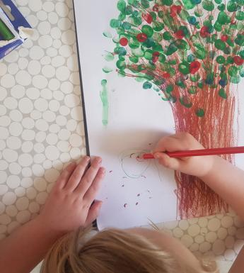 Photo of child's hands drawing a tree