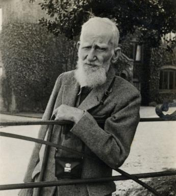 George Bernard Shaw leans on a gate, looking at the viewer. He is wearing a tweed suit, and has a camera around his neck