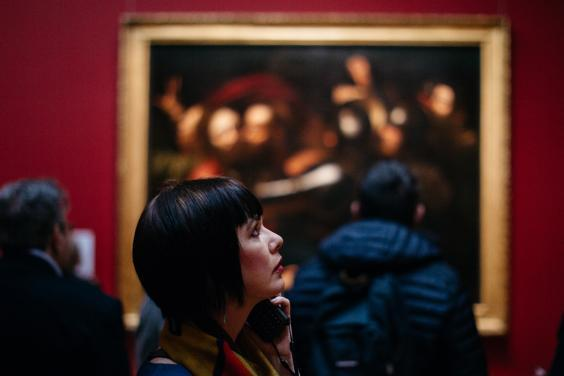 A visitor to Beyond Caravaggio examines a painting. © National Gallery of Ireland.