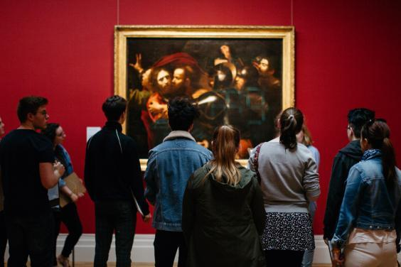 Visitors in front of the Taking of Christ in the exhibition Beyond Caravaggio. © National Gallery of Ireland.