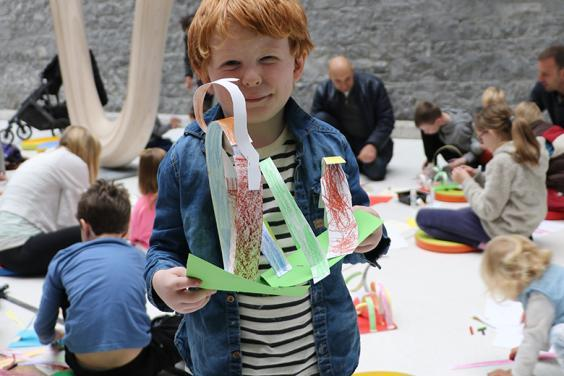 A young boy holds up the artwork he created a drop-in family workshop in the National Gallery of Ireland.