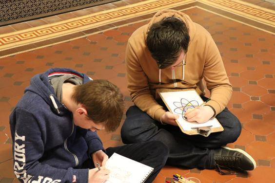 Photo of two teenage boys sitting on the floor drawing