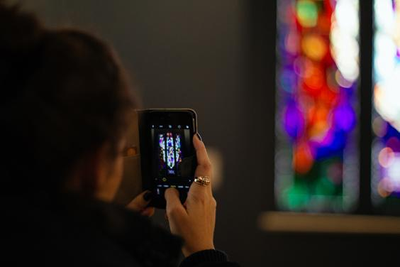 Photo of a woman using her phone to take a photo of stained glass in the National Gallery of Ireland.