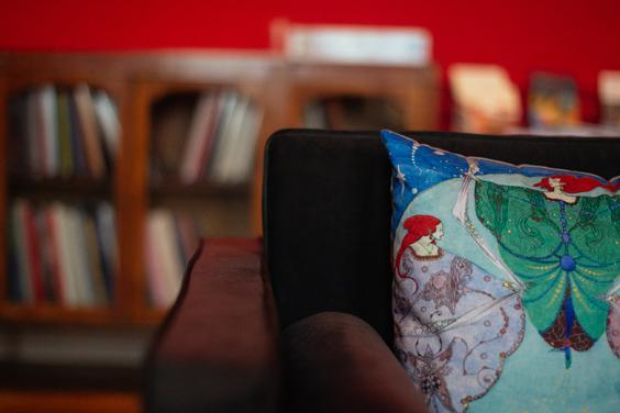 Photo of the corner of a sofa with a cushion decorated with a painting by Harry Clarke. A book case is out of focus in the background.