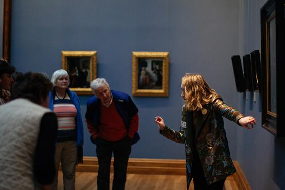 Photo of a tour guide speaking to a group of visitors in front of Dutch seventeenth-century paintings in the National Gallery of Ireland.