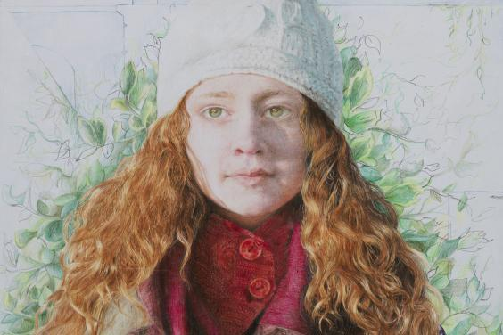 A young woman facing us, with her hands (in woolen mittens) clasped in front of her. She is wrapped in a number of different scarves, and wears a white wool hat. Her long auburn hair falls over her shoulders, and behind her there is green foliage.