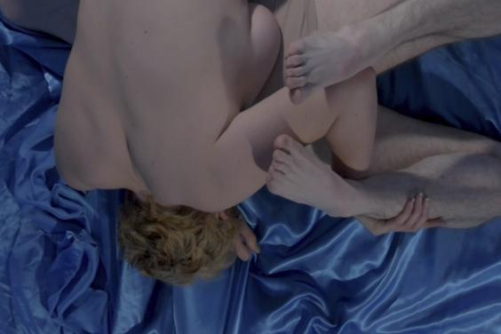 Two people lie across each other on a blue satin sheet, limbs intertwined. They are naked except for flesh-coloured underpants.