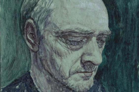 A close-up portrait of a man's face. There is a greenish hue to the portrait, and the man wears a blue jumper. His eyes are closed, and the expression on his face is somber.