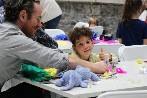 Photo of a boy and his father making art at a table.