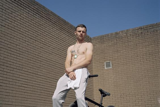 The subject of the portrait looks down a the camera lens, which is below him. He is leaning on the handlebars of a black bike which is behind him. He wears grey tracksuit pants and navy runners, and has a white tshirt tucked into his waistband. His hands are clasped in front of him, and he has a tatoo on his chest. Around his neck he wears a scapular and a rosary neads. Above his head, we see a section of blue sky above the brick wall behind him.