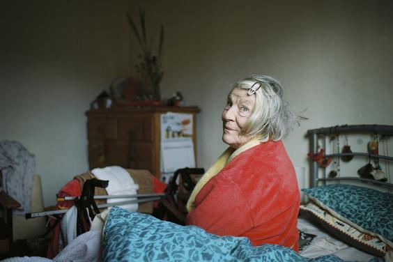 A woman in a red and yellow dressing gown sits on an unmade bed with a blue cover, looking at the viewer over her shoulder with an amused expression on her face. In the background we see a chest of drawers with a calendar attached to the side, and flowers and other belongings on top. The room is filled with signs of life - chairs, clothes, beads hanging on the bedspread etc.