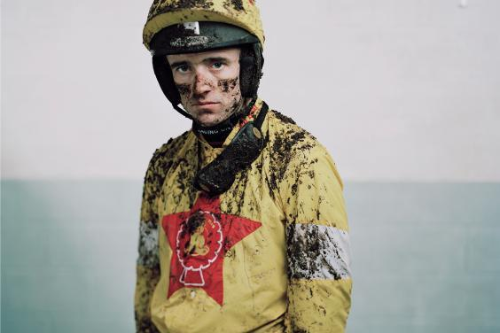 Photo of a jockey covered in mud