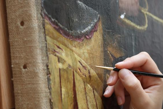 A detail of a conservator's hand with a brush, working on adjusting old discoloured retouchings on Lavinia Fontana's The Visit of the Queen of Sheba to King Solomon
