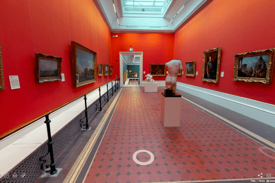 A view of a vibrant red gallery lined with paintings. On the tiled floor stand some sculptures